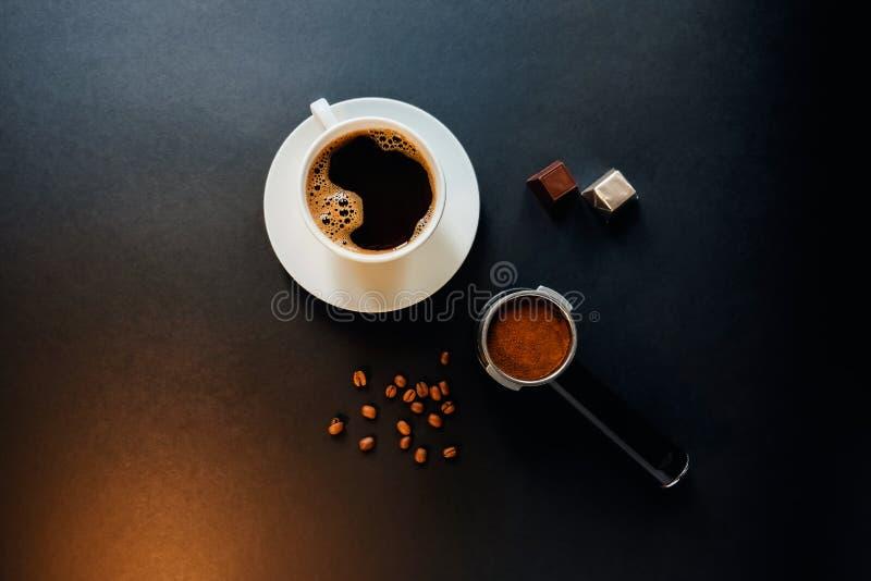 Geschmackvoller Kaffee auf der schwarzen Tabelle mit Schokolade lizenzfreies stockbild