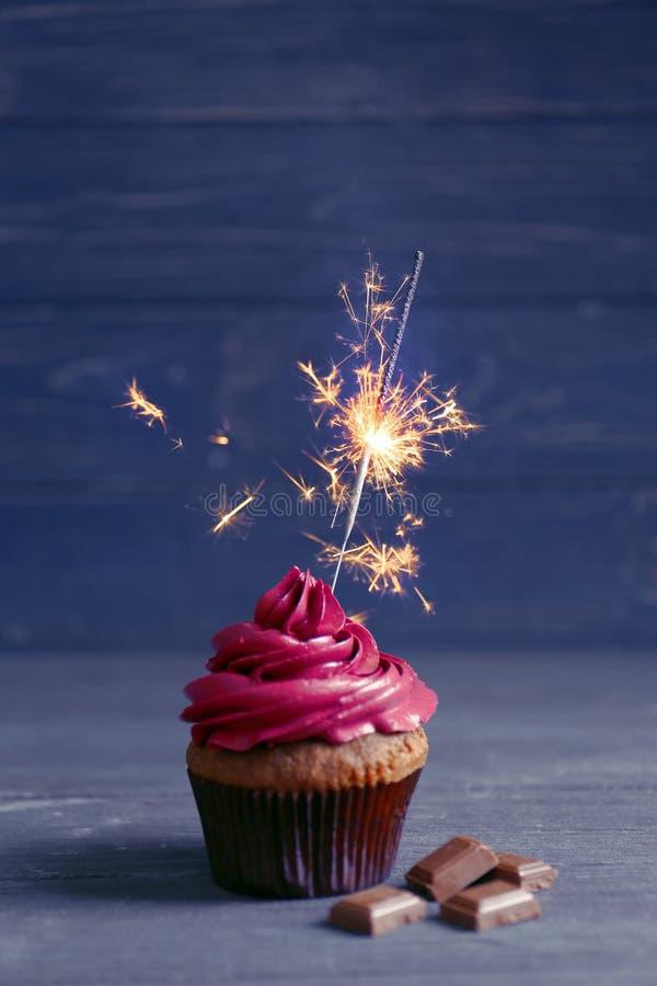 Geschmackvoller kleiner Kuchen mit Wunderkerze und Schokolade stockfotografie
