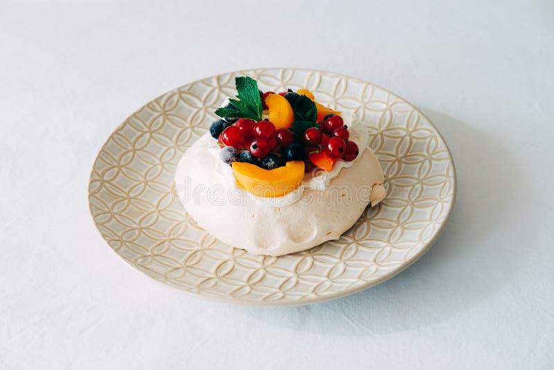 Geschmackvoller Pavlova-Nachtisch mit weißer Meringe, Creme und Frucht lizenzfreie stockfotografie
