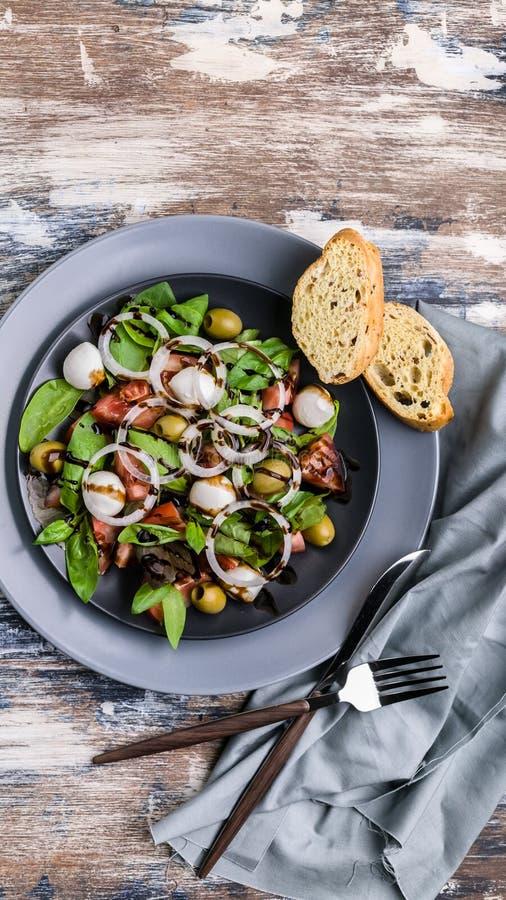 Geschmackvoller Salat der Draufsicht von den frischen Kräutern mit Mozzarella, Tomaten, Oliven und Zwiebeln Traditionelle Mittelm stockbilder