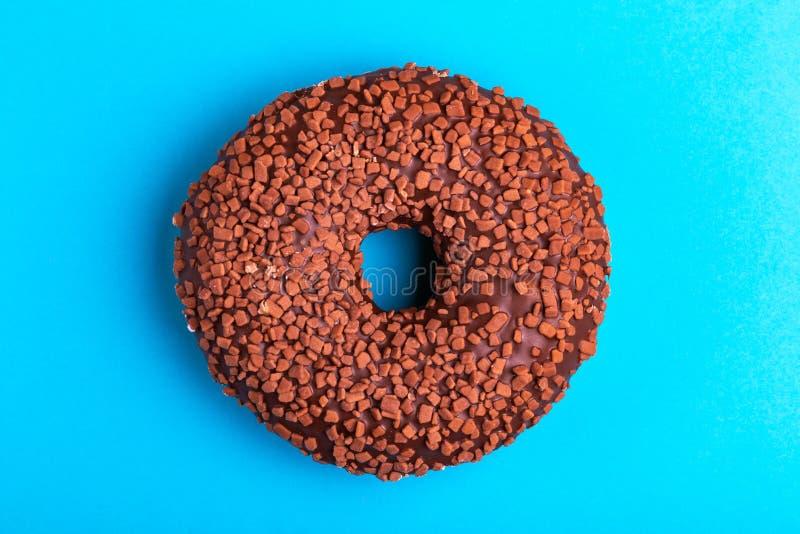 Geschmackvoller Schokoladendonut auf hellem blauem Hintergrund stockfotografie