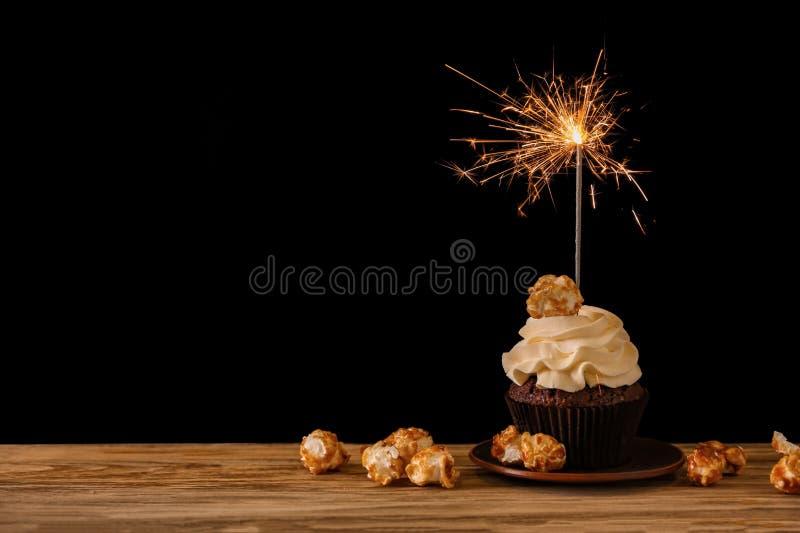 Geschmackvoller Schokoladenkleiner kuchen mit Wunderkerze und Popcorn auf Holztisch gegen dunklen Hintergrund stockbilder