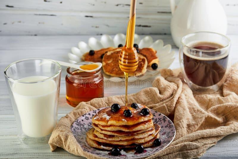 Geschmackvoller Stapel des Frühstücks A Pfannkuchen mit Honig süßen ein Glas Milch, Espressokaffee und Honig auf einem hölzernen  lizenzfreie stockfotos