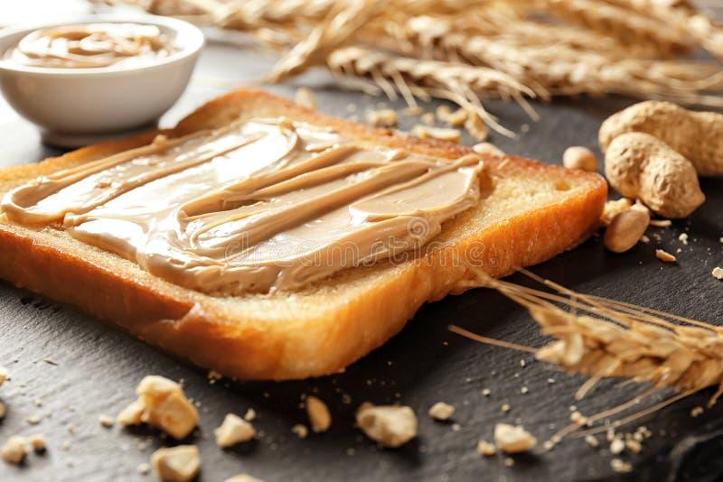 Geschmackvoller Toast mit Erdnussbutter auf Schieferplatte, Nahaufnahme stockfotografie