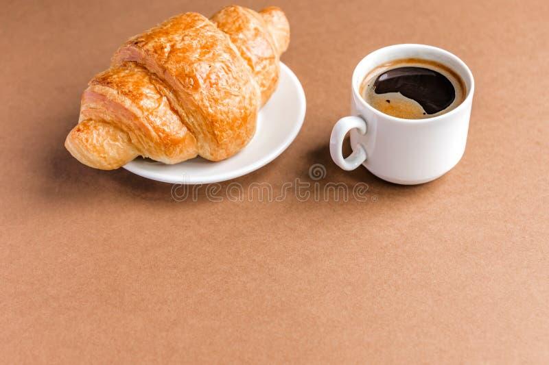 Geschmackvolles breackfast französisches Hörnchen gedient auf weißer Platte und Schale schwarzem Kaffee oder Espresso auf braunem stockbilder