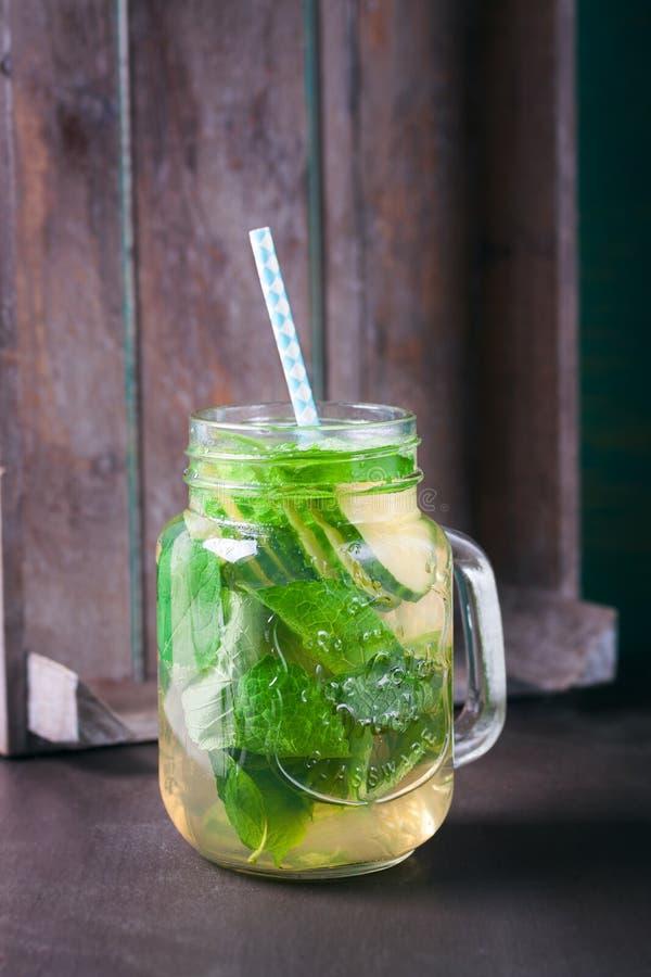 Geschmackvolles buntes Getränk mit kaltem grünem Tee, Minze und Gurke in einem Glasgefäß auf einem Weinlesehintergrund stockfotografie