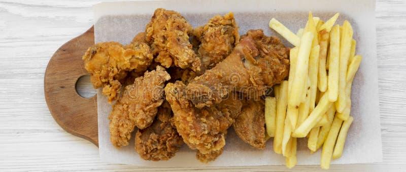 Geschmackvolles Fastfood: gebratenes Hühnertrommelstöcke, würzige Flügel, Pommes-Frites und Hühnerstreifen über weißem hölzernem  lizenzfreie stockfotos