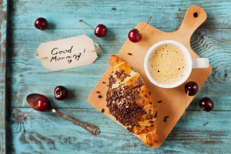Geschmackvolles Frühstück mit neuem Hörnchen, Kaffee, Kirschen und Anmerkungen über einen Holztisch lizenzfreies stockbild