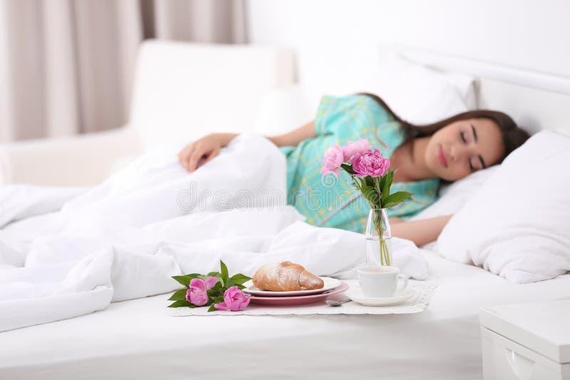 Geschmackvolles Frühstück und schlafende junge Frau im Bett lizenzfreie stockbilder