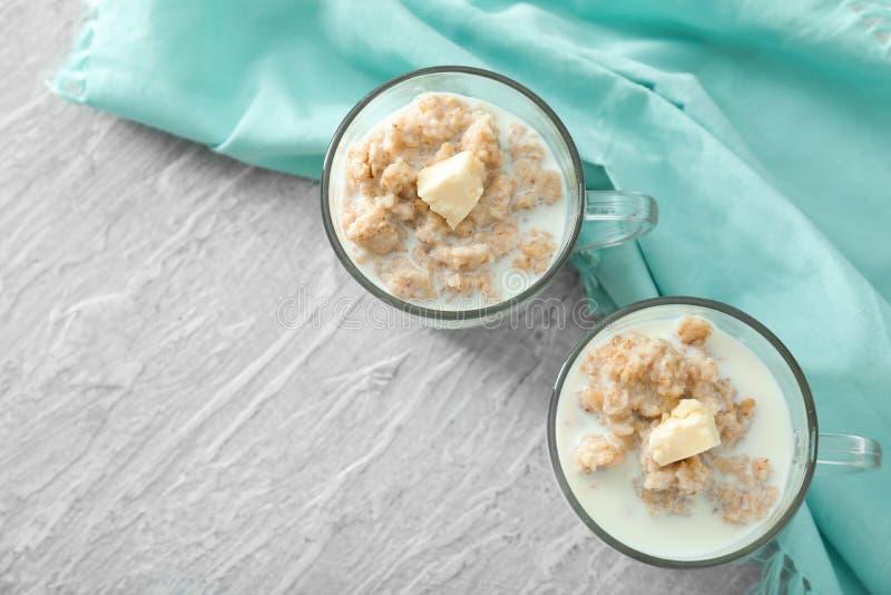Geschmackvolles Hafermehl mit Milch und Butter in den Glasschalen auf Tabelle stockbild