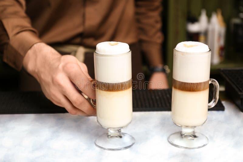 Geschmackvolles Kaffeegetr?nk Barista-Umh?llung auf Tabelle lizenzfreie stockfotografie