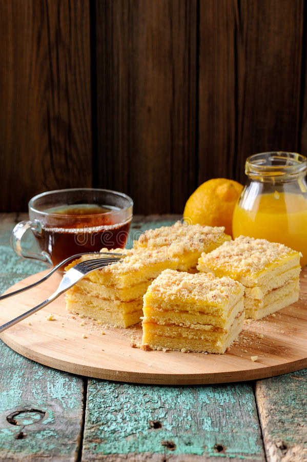 Geschmackvolles Quadrat überlagerte Zitronenkuchen mit schwarzem Tee und Zitronenklumpen an lizenzfreies stockbild