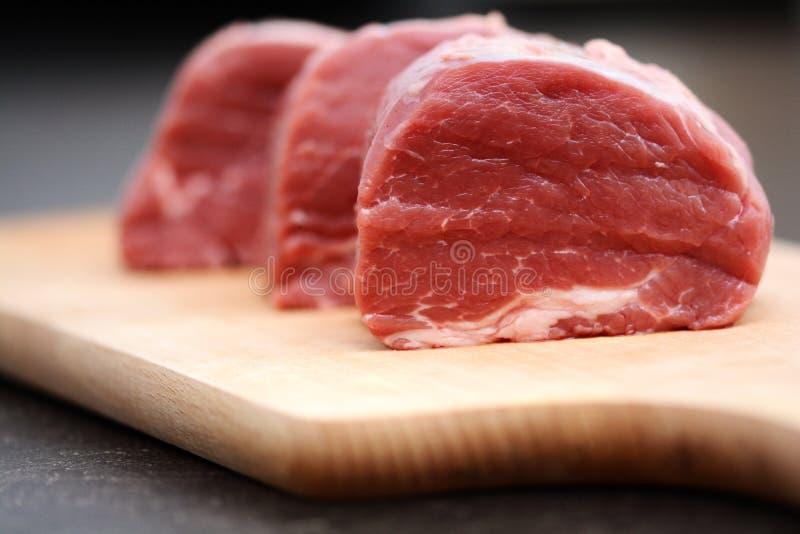 Geschmackvolles rohes Rindfleischfleisch auf hölzernem Schneidebrett lizenzfreie stockbilder