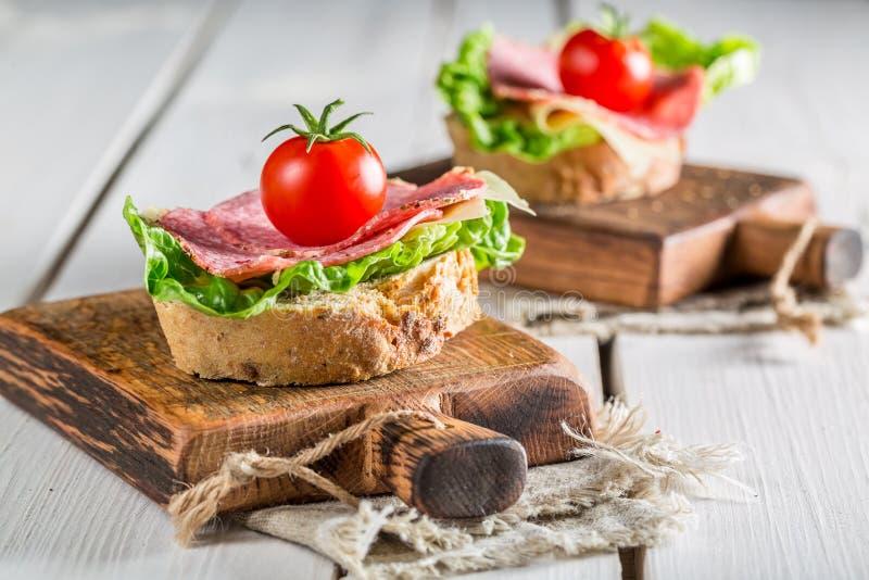 Geschmackvolles Sandwich mit Salami, Tomate und Kopfsalat stockfoto