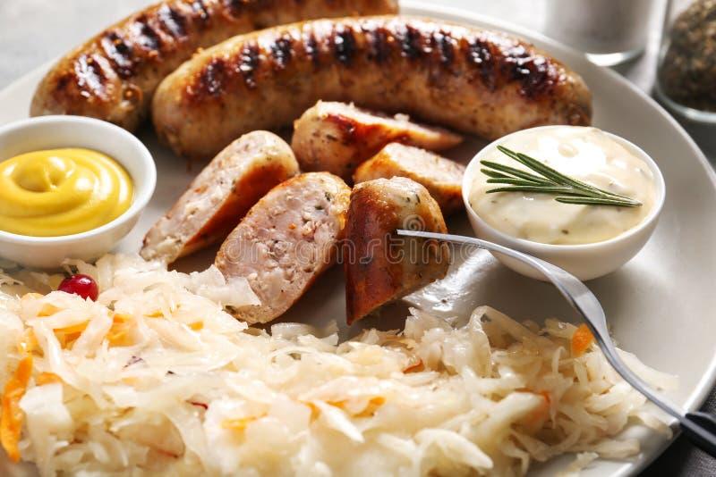 Geschmackvolles Sauerkraut mit gegrillten Würsten und Soßen auf Platte, Nahaufnahme lizenzfreie stockfotos