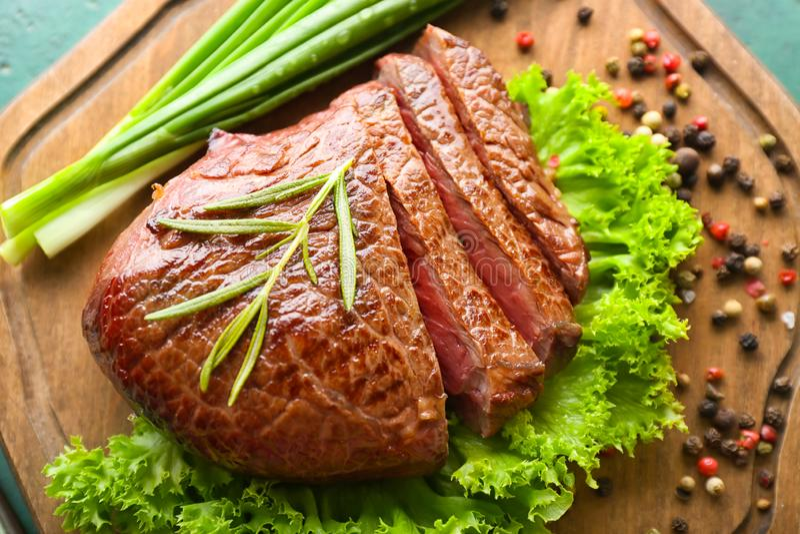 Geschmackvolles Steak mit Kräutern, Frühlingszwiebel und Gewürzen an Bord, Nahaufnahme stockfotografie