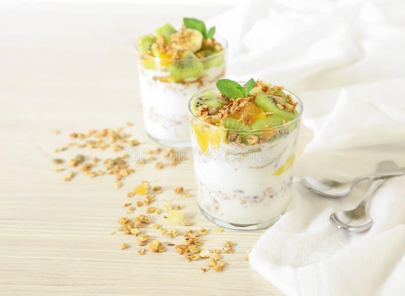 Geschmackvolles und gesundes Frühstück oder Snack zwei Gläser des Joghurts, des Granolas und der Kiwi, Orange, Bananenscheiben, H stockfotografie