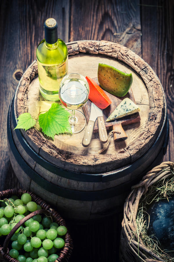 Geschmackvolles Weißwein mit Käse, Trauben und Korbflasche stockfoto