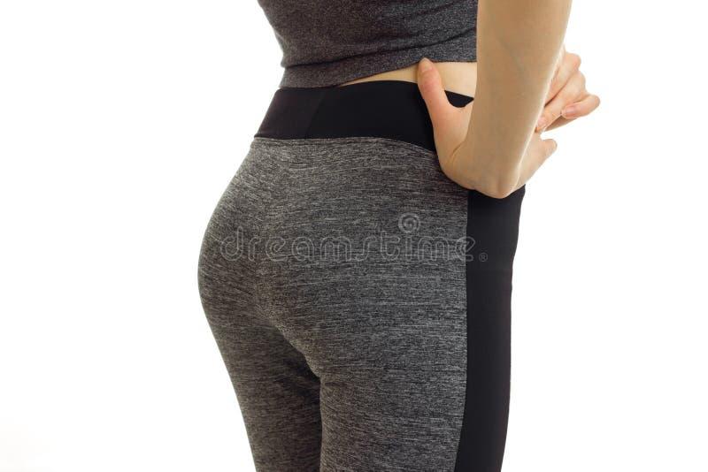 Geschmeidige Hinterteile des Sports eines jungen Mädchens in der Hose ist auf einem weißen Hintergrund stockfotos