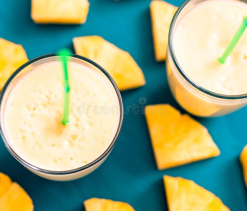geschnittene Ananas mit einem Glas Ananassaft auf einem blauen hölzernen Hintergrund stockfotografie