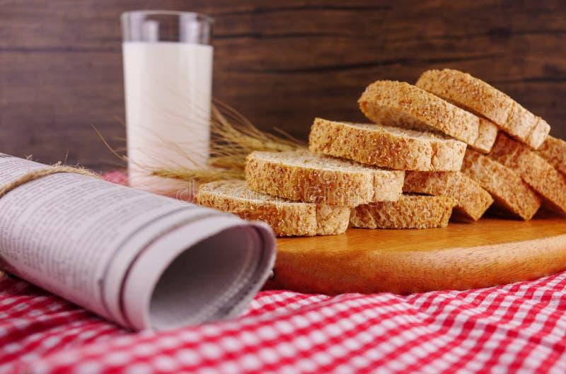 Geschnittene Brote auf hölzerner Platte mit Milch lizenzfreie stockbilder