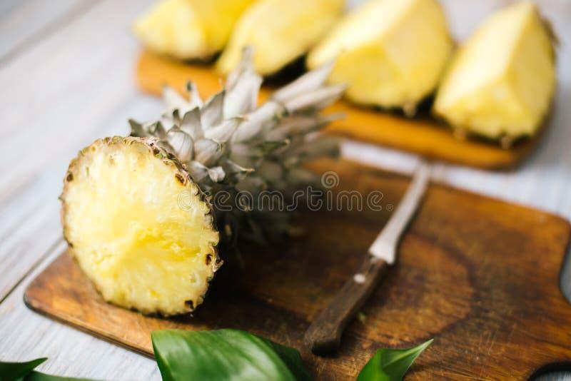 Geschnittene frische Ananas auf einem hölzernen Hintergrund im Sonnenlicht stockfotografie