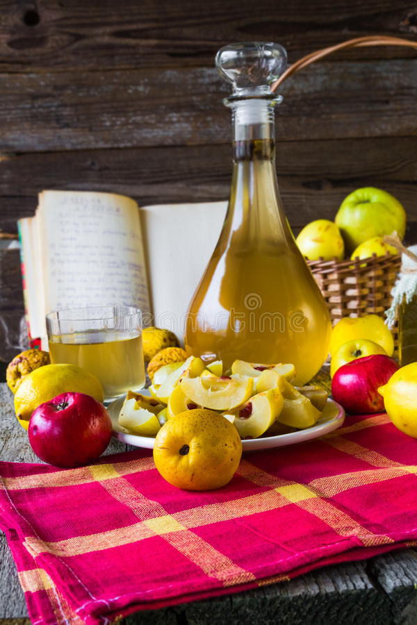 Geschnittene Frucht der Alkoholquitte Likör bereiten hölzerne Einstellung vor stockfotografie