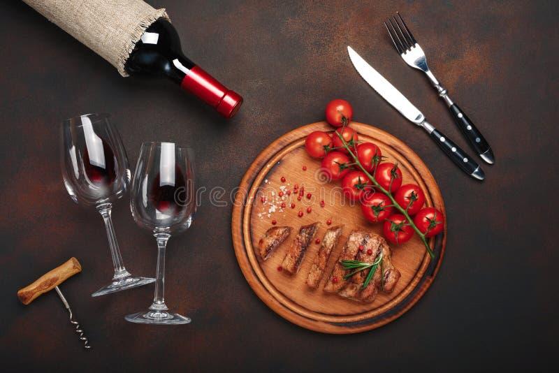 Geschnittene gegrillte Schweinefleischsteaks mit Flasche Wein, Weinglas, Korkenzieher, Messer, Gabel, Schwarzbrot, Kirschtomaten, lizenzfreie stockfotos