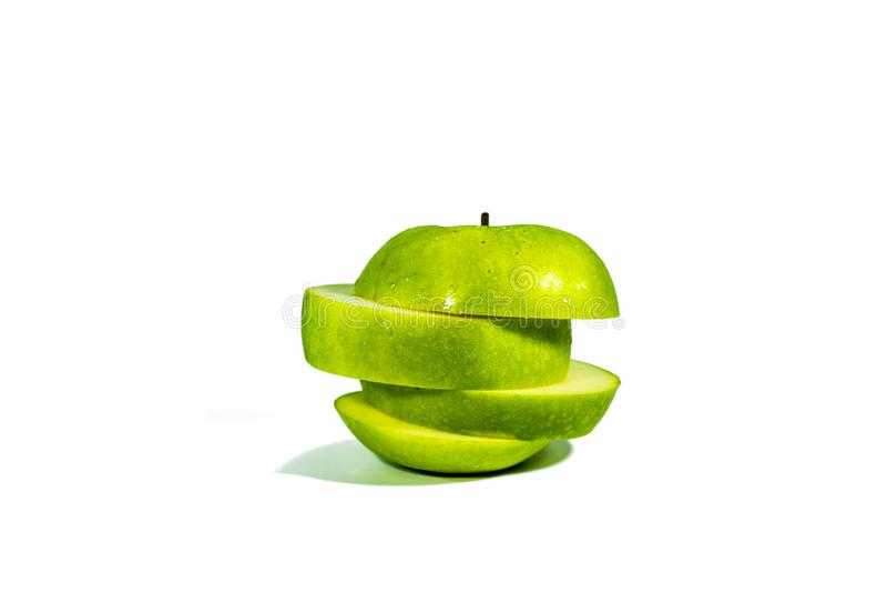 Geschnittene grüne Äpfel, gestapelt lokalisiert auf einem weißen Hintergrund stockfotografie