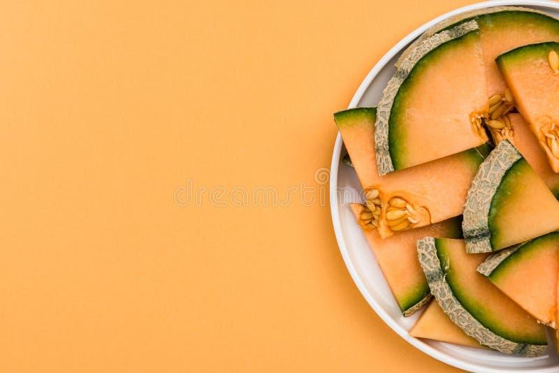 Geschnittene Kantalupen-Melone gedient auf Platte, Pastell-Hintergrund, Grenzhintergrund lizenzfreies stockfoto
