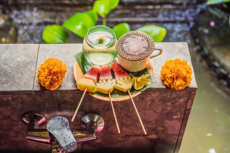 Geschnittene Mango-Wassermelonen-Papaya-Melone trägt auf nass grünes Palmblatt verzierter rosa Frangipani-Blumen-tropischer Natur lizenzfreie stockbilder