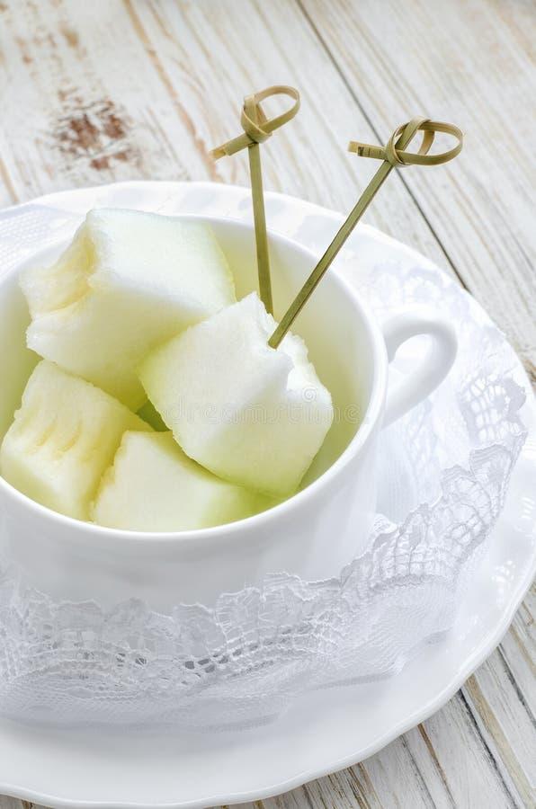 Geschnittene Melone auf weißer Platte lizenzfreie stockfotos
