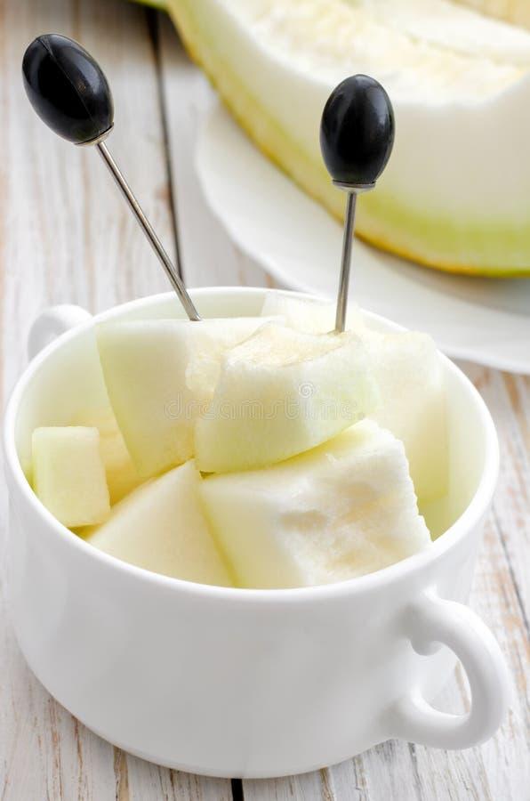 Geschnittene Melone auf weißer Platte lizenzfreie stockbilder