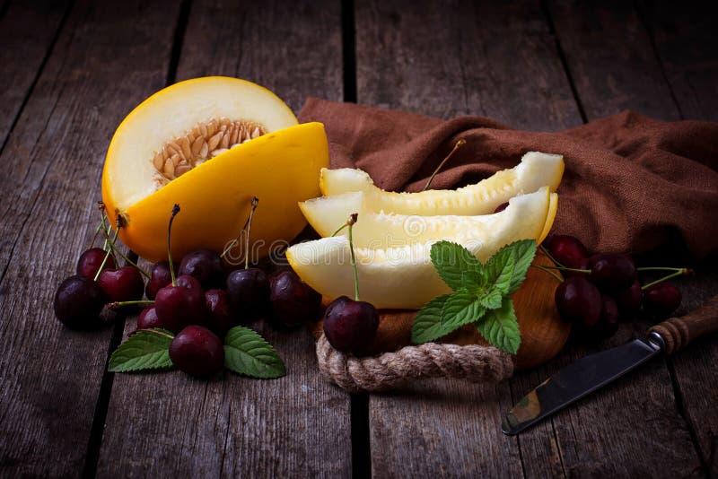 Geschnittene Melone mit Minze und Kirsche stockbild