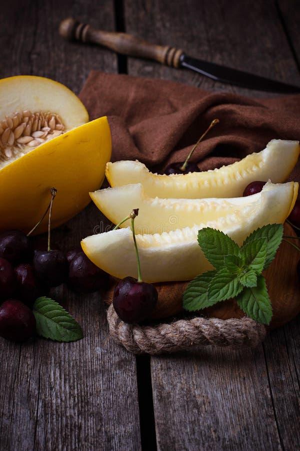 Geschnittene Melone mit Minze und Kirsche stockfotos