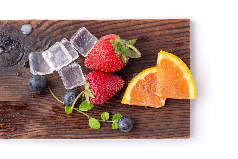 Geschnittene Orange, Erdbeere und Blaubeere auf einer hölzernen Platte mit i lizenzfreie stockfotos