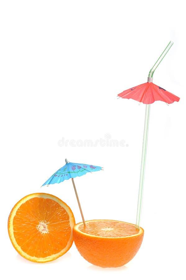 Geschnittene Orange mit Cocktailregenschirm stockbild
