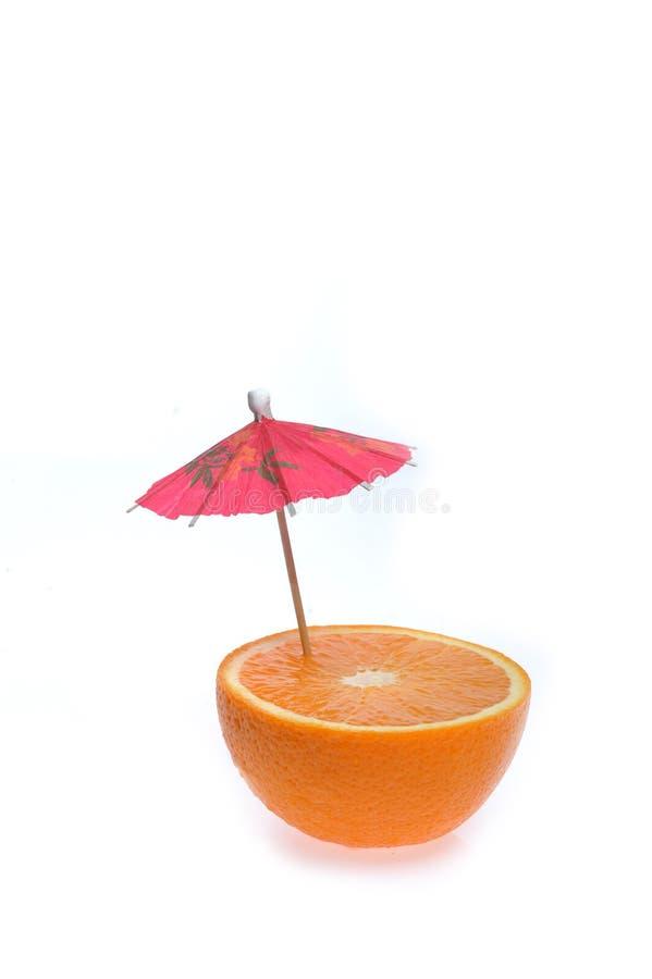 Geschnittene Orange mit coctail Regenschirm lizenzfreie stockfotografie