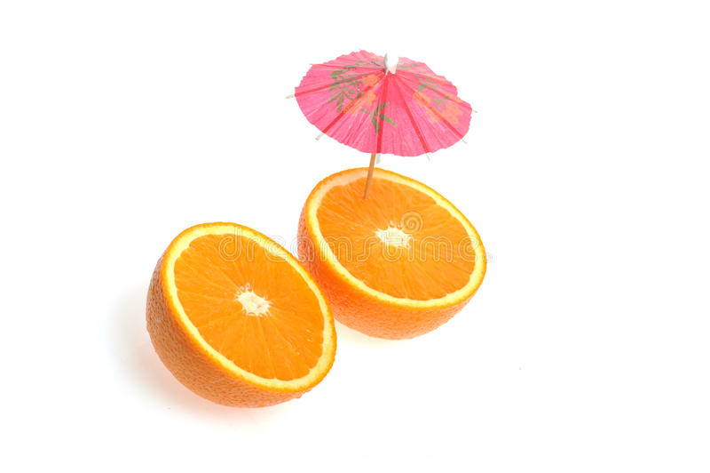 Geschnittene Orange mit coctail Regenschirm stockfotografie
