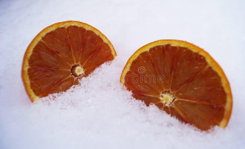 Geschnittene Orangen im Schnee Früchte im Winter stockfotos