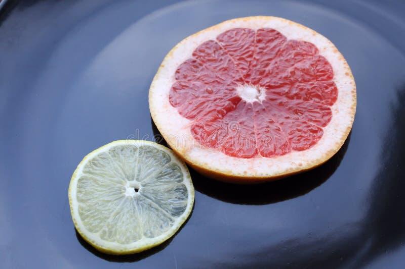 Geschnittene Pampelmuse und Zitrone auf schwarzem glattem Hintergrund stockfotografie