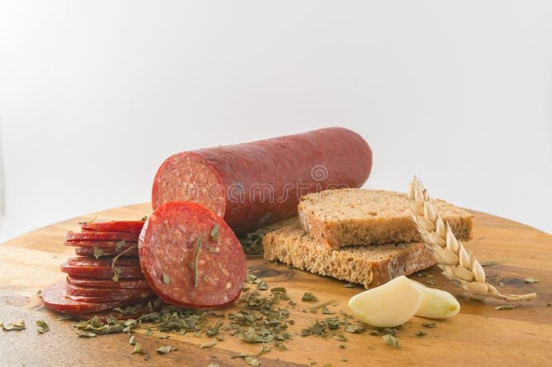 Geschnittene Salami mit Brot auf Holztisch lizenzfreie stockfotos