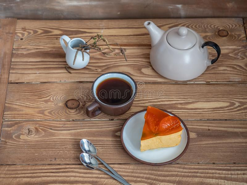 Geschnittene Scheibe von mozzake Kuchen auf einer kleinen keramischen Schüssel, Tee in einer braunen Schüssel und Sahneteekanne stockbild