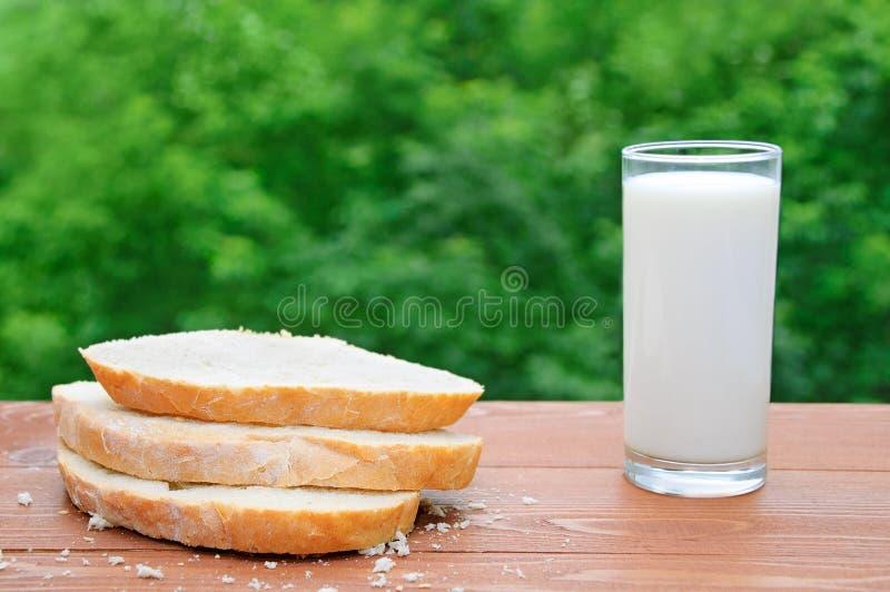 Geschnittene Scheiben des Weizenbrotes und des Glases Milch lizenzfreie stockfotos