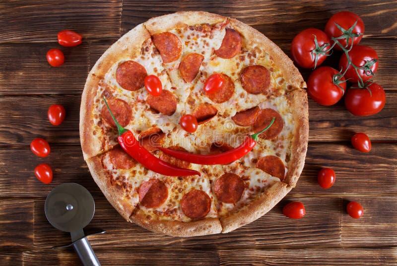 Geschnittene selbst gemachte hei?e mexikanische Pizza mit einer l?chelnden M?ndung von Pfeffer- und Tomatenl?gen auf einer Holzob lizenzfreie stockbilder