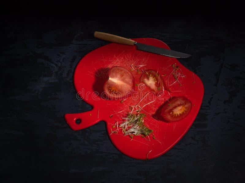 Geschnittene Tomate auf einem roten dekorativen Brett, kressalat Dunkler Hintergrund, Küchenmesser stockfotografie