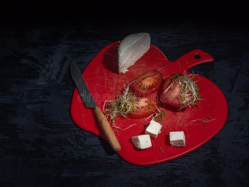 Geschnittene Tomate und Adyghe-Käse auf einem roten dekorativen Brett, kressalat Dunkler Hintergrund, nahe bei dem Küchenmesser lizenzfreies stockfoto