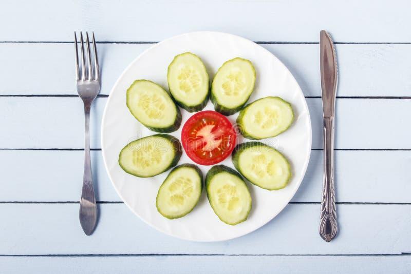 Geschnittene Tomate und Gurke zum gesundes Frühstück auf weißer Platte Gabel und Messer auf Holztisch Beschneidungspfad eingeschl stockfotos