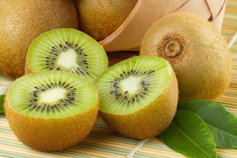 Geschnittene und vollständige Früchte der Kiwi stockbilder