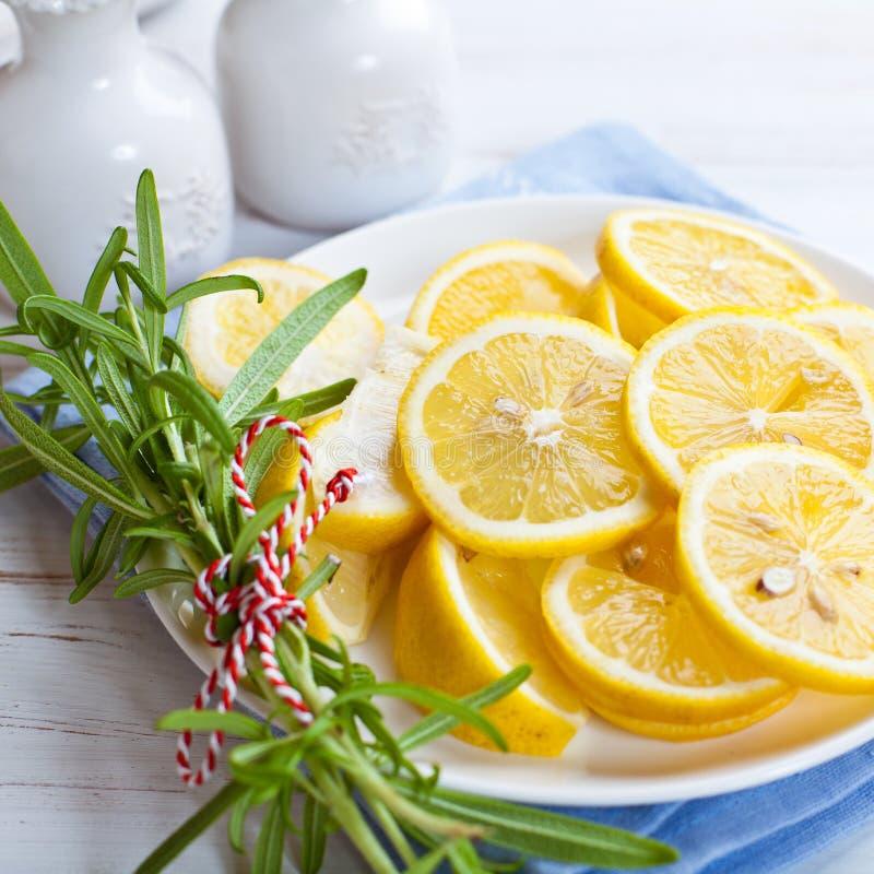 Geschnittene Zitronen mit Rosmarin auf einer Platte lizenzfreie stockfotos